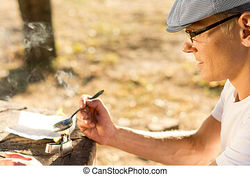 Middle-aged man heating a dose of crack cocaine