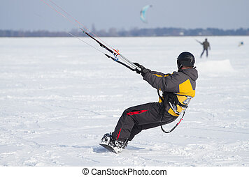 Snowkiting on a snowboard on a frozen lake