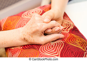 Young hands caring for old hands on a red cushion