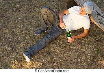 High angle view of an alcoholic man lying down on the ground...