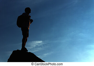 Lonely male hiker standing on the mountain top - Silhouette...
