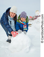 Family make a snowman - Happy beautiful boy with mother...