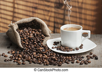 coffee beans on wooden table with cup of coffee