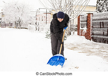 Snow removal - Young man remove snow near the suburban house