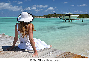 Girl on the wooden jetty looking to the ocean Exuma, Bahamas...