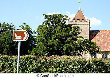 Tourist sign points towards historic church - Brown tourist...