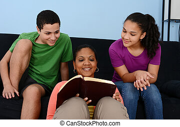 Bible Study - Family studying the bible together in their...