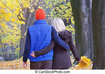 Couple in autumn park - Loving couple walking arm in arm in...