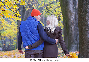 Couple in autumn park - Happy couple walking a beautiful...