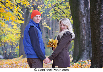 Man and a woman in the autumn park - Lovers male and female...