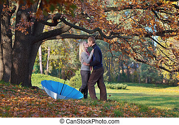 Couple kisses - Happy couple kissing in autumn park under a...