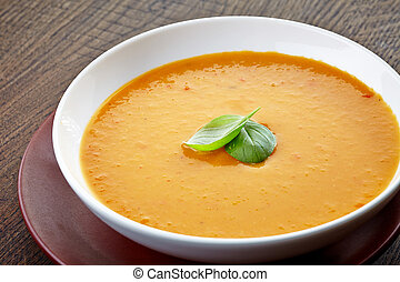 squash soup with basil leaf in a bowl