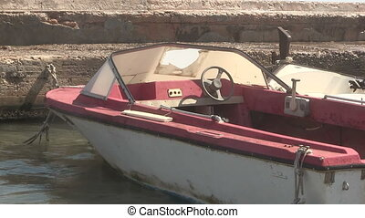 Old motor boat moored at a quayside.