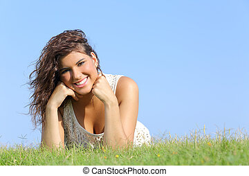Portrait of an attractive woman lying on the grass with a...