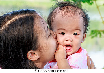 Mother kissing daughter - Asian woman holding and kissing...