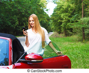 Beautiful blond young woman standing near a sports car with...