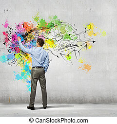 Back view of businessman drawing colorful business ideas on...