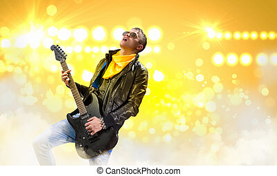 Rock star - Young man, rock musician in jacket playing...