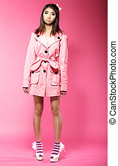 Young Asian Female Fashion Model in Pink Coat standing in Studio