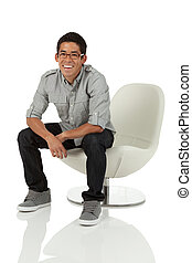 Young adult sitting on chair - Young adult sitting on modern...