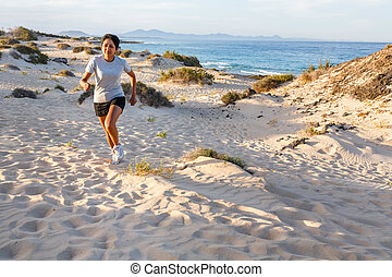 Woman running on beach - Young Indian female jogging...