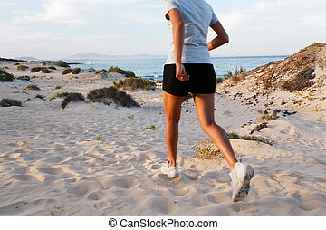 Running outdoors - Female Indian jogger jogging on a beach