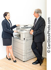 Colleagues talking at copying machine in the office - A...