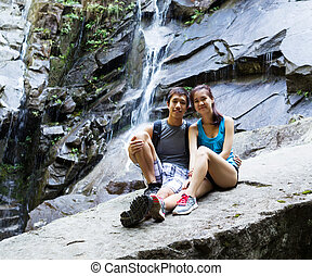Young Active Hikers Resting Near Waterfalls