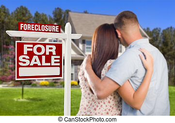 Military Couple Standing in Front of Foreclosure Sign and...