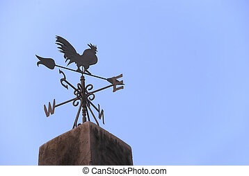 Wind vane in a form of a rooster on the top of a roof.
