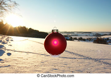 Christmas - a red bauble in snowy landscape