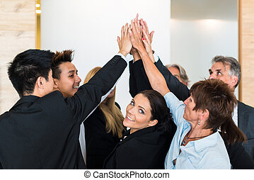 Teamwork - business people with joint hands in the office -...