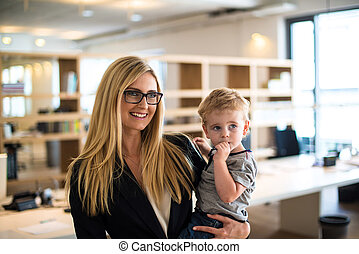 Businesswoman with small child in the office -...