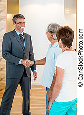 Banker and Senior Couple - Banker is saying good bye to a...