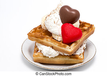 Waffle with sweet cream and red heart shaped marzipan candy