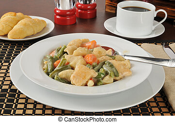 Chicken and dumplings - A bowl of chicken and dumplings with...