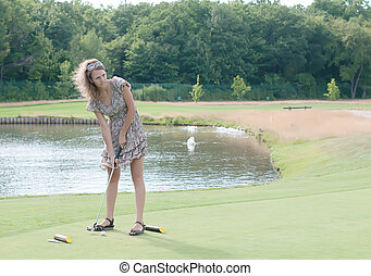 Full length view of 5 year old girl swinging golf club