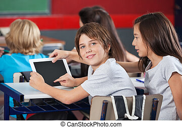 Boy With Girl Using Digital Tablet At Desk - Side view...