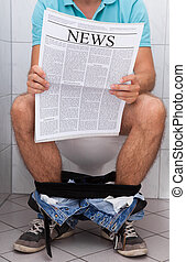 Close-up of a man in toilet reading newspaper indoors