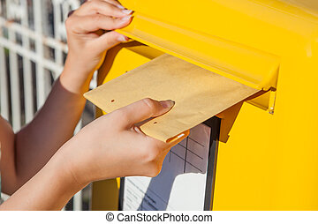 Woman inserting envelope in mailbox - Close-up of woman's...
