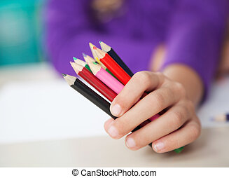 Girl Holding Colored Pencils At Desk