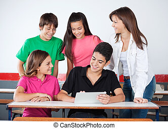 Teenage Boys And Girls Using Digital Tablet At Desk - Happy...