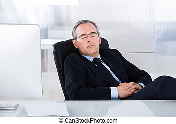 Businessman Sleeping At Desk In Office - Mature Businessman...