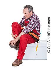 Male Technician suffering from knee pain - Male Technician...