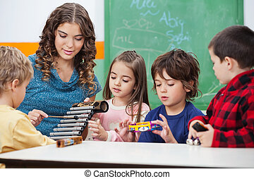 Teacher Teaching Students To Play Xylophone In Class -...