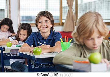 colegial, Sentado, en, escritorio, con, compañeros de...