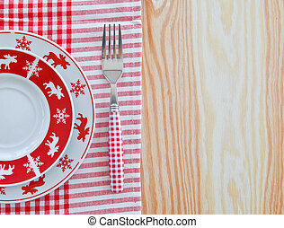 Plates with christmas pattern on wooden background