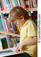 Reading in library - Portrait of clever boy reading book in...