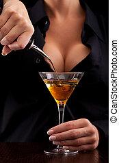 Barmaid mixing drink - Barmaid stands behind bar mixing...