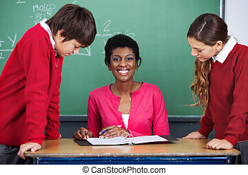 Teacher Sitting At Desk With Students - Portrait of happy...